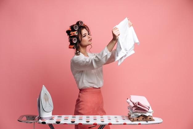 Een mooie huisvrouw strijkt kleren, onderzoekt zorgvuldig gestreken kleren