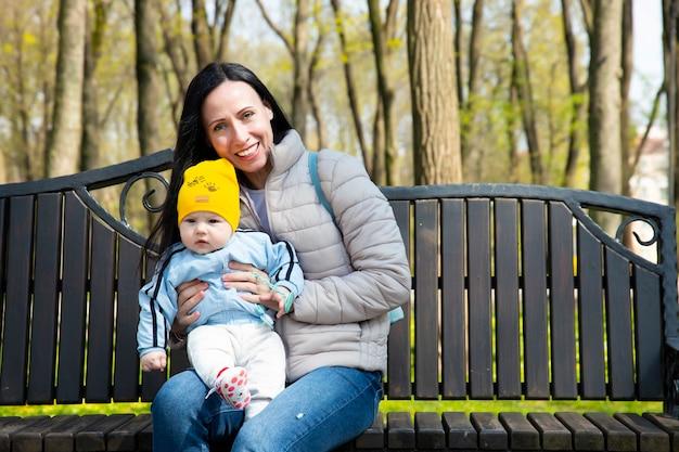 Een mooie, jonge aantrekkelijke moeder, met een kleine jongen, zoon, zit op een bankje in een lentepark.
