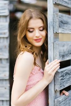 Een mooie jonge blanke meisje met professionele make-up met haar ogen bedekt staat in de buurt van een houten poort in de stad