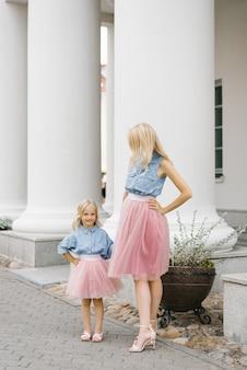 Een mooie jonge blonde moeder en haar charmante dochter in dezelfde romantische kleding staan bij de zuilen en glimlachen