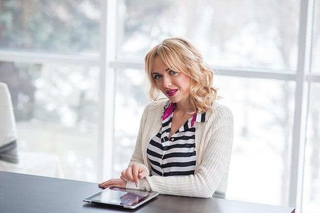 Een mooie jonge blonde vrouw die aan de tafel zit met een laptop.