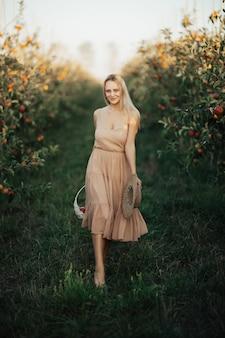 Een mooie jonge blonde vrouw in een bleke roze jurk loopt in de appeltuin tijdens het herfstseizoen.