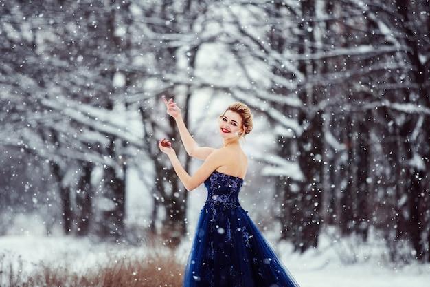 Een mooie jonge blonde vrouw in een weelderige blauwe jurk poseren in een besneeuwd winterpark