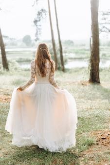 Een mooie jonge bruid in witte jurk in een bos