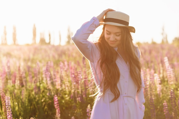 Een mooie jonge brunette vrouw. aantrekkelijk sexy meisje in een veld met bloemen