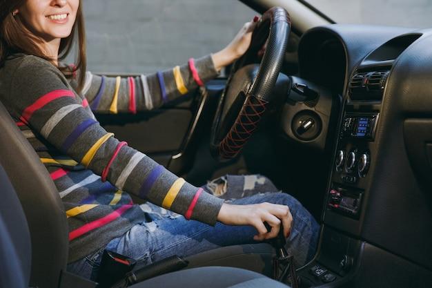Een mooie jonge gelukkig lachende europese bruinharige vrouw met een gezonde schone huid gekleed in een gestreept t-shirt zit in haar auto met zwart interieur. reizen en rijden concept.