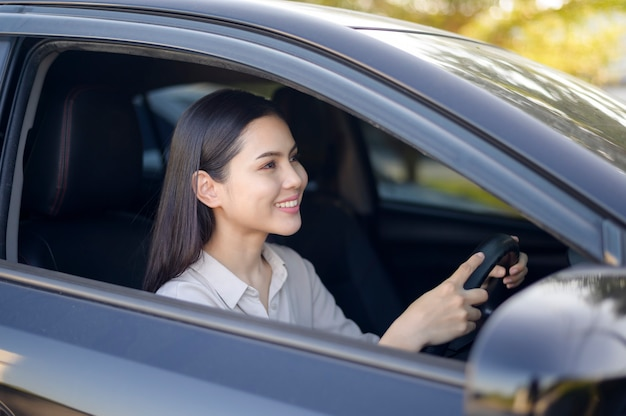 Een mooie jonge glimlachende vrouw die haar auto, verzekeringen en financiënconcept drijft