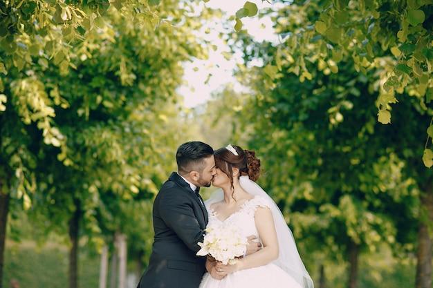 Een mooie jonge man draagt een zwart pak en een baard in het park, samen met zijn bruid