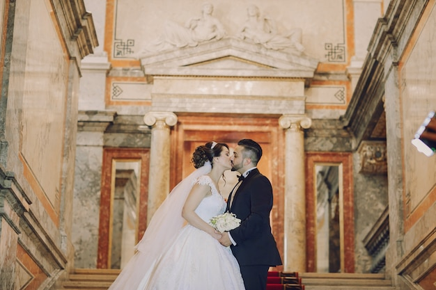 Een mooie jonge man draagt een zwart pak staat samen met zijn bruid