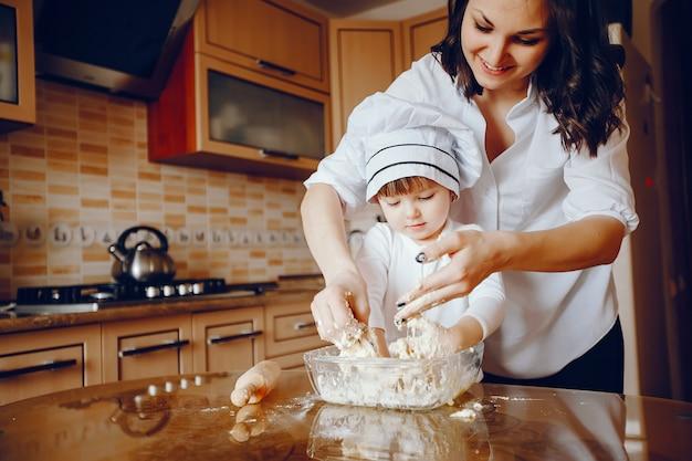 Een mooie jonge moeder met haar kleine dochter kookt thuis in de keuken