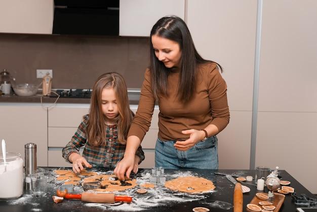 Een mooie jonge moeder snijdt het koekjesdeeg met haar dochter in keuken die een geweldige tijd hebben