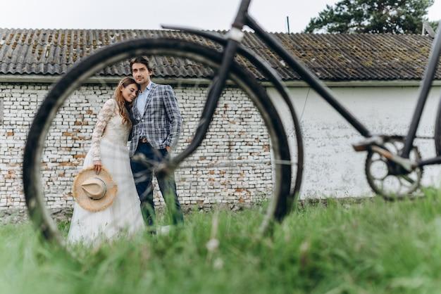 Een mooie jonge paar bruid en bruidegom met een fiets in de buurt van oud huis