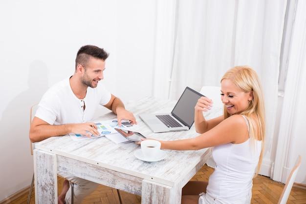 Een mooie jonge paar zittend aan een tafel zaken bespreken.