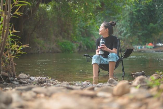 Een mooie jonge reiziger vrouw geniet met de natuur koffie te drinken in de ochtend boven het meer, ontspanning, kampeervakantie en reisconcept