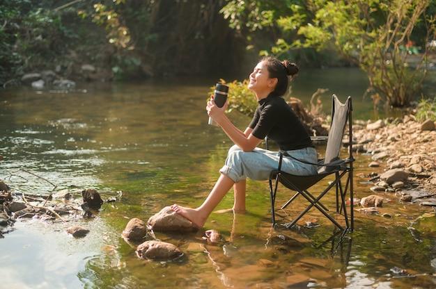 Een mooie jonge reizigersvrouw geniet met de natuur van het drinken van koffie in de ochtend over meer
