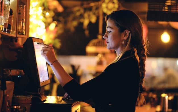 Een mooie jonge vrouw aan de balie in een restaurant