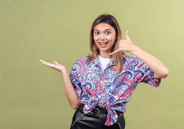 Een mooie jonge vrouw die een paisley-bedrukt overhemd draagt dat call me-gebaar toont