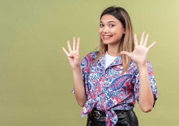 Een mooie jonge vrouw die een paisley-bedrukt overhemd draagt met nummer negen