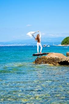 Een mooie jonge vrouw die in de zomer geniet van de wind en het klimaat aan de oceaan.