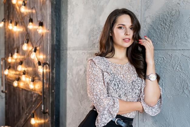 Een mooie jonge vrouw die op muur leunt die zich dichtbij de deur bevindt die met gloeilamp wordt verfraaid