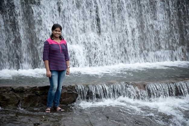 Een mooie jonge vrouw die zich voordeed aan de oever van de rivier en geniet van of speelt met het water dat overstroomt uit de rivier.