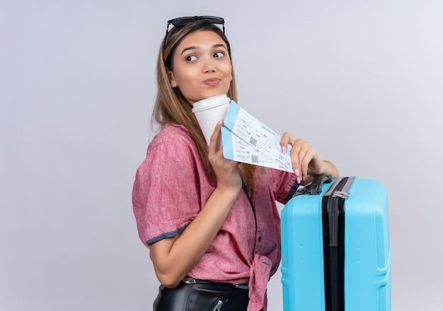 Een mooie jonge vrouw draagt een rood shirt met een zonnebril opzij terwijl ze een blauwe koffer en vliegtickets op een witte muur vasthoudt