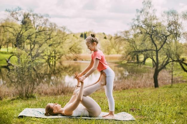 Een mooie jonge vrouw en haar dochter beoefenen yoga in sportkleding met behoud van een gezonde levensstijl