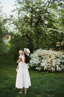 Een mooie jonge vrouw en schattige peuterjongen, jonge moeder en haar zoontje, poseren in een stadspark op een warme zomerdag.