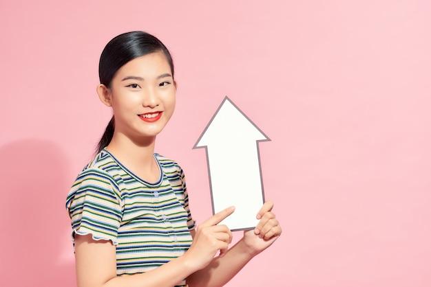 Een mooie jonge vrouw houdt een witte pijl omhoog. concept van economische groei