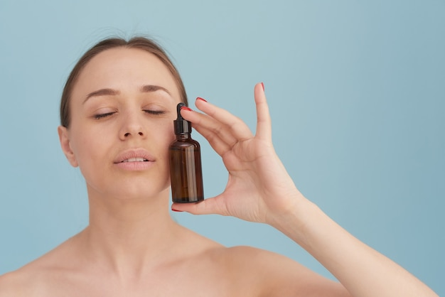 Een mooie jonge vrouw hydrateert haar huid met een serum. verzorging van de huid. etherische olie voor anti-aging therapie.