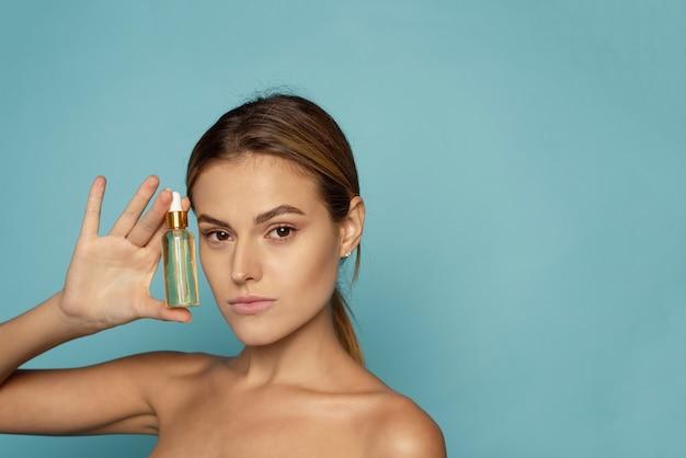 Een mooie jonge vrouw hydrateert haar huid met een serum. verzorging van de huid.