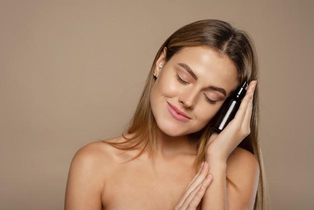 Een mooie jonge vrouw hydrateert haar huid met een serum