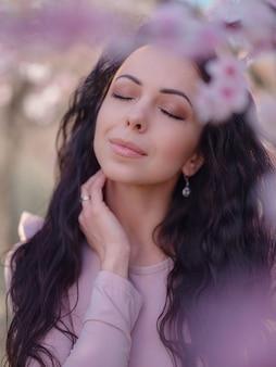 Een mooie jonge vrouw in de buurt van een bloeiende lente kersenbloesem boom. een feest van lente en bloesem zoals in japan