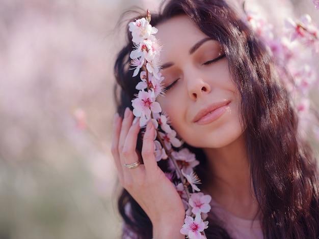 Een mooie jonge vrouw in de buurt van een bloeiende lente kersenbloesem boom. een ongelooflijk zacht licht portret