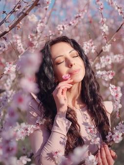 Een mooie jonge vrouw in de buurt van een bloeiende lente kersenbloesem boom. het idee en concept van vernieuwing, zelfzorg en geluk
