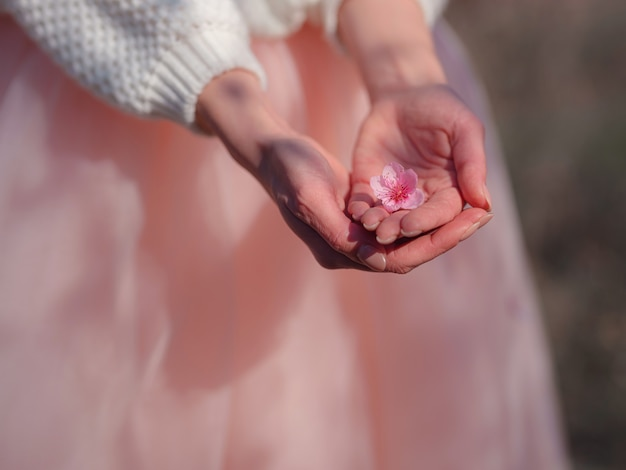 Een mooie jonge vrouw in de buurt van een bloeiende lente kersenbloesem boom. het idee en concept van vernieuwing, zelfzorg, gezondheid en geluk, close-up handen