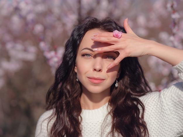 Een mooie jonge vrouw in de buurt van een bloeiende lente kersenbloesem boom. het idee en concept van vernieuwing, zelfzorg, gezondheid en geluk, japanse stijl