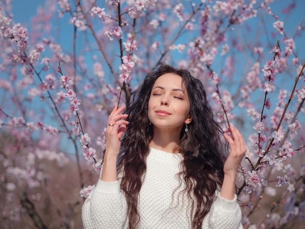 Een mooie jonge vrouw in de buurt van een bloeiende lente kersenbloesem boom. het idee en concept van zelfzorg, gezondheid en geluk