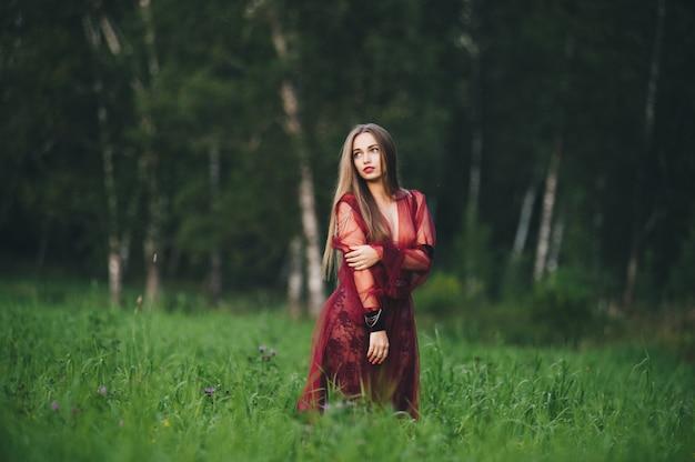 Een mooie jonge vrouw in een bard-jurk staart in het veld en de tuin.