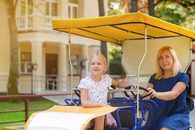 Een mooie jonge vrouw in een blauwe spijkerjurk met een klein meisje zittend op een vierpersoons wandelwagen