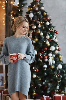 Een mooie jonge vrouw in een gebreide jurk houdt een kop warme drank en poseren in de buurt van de kerstboom op interieur ingericht voor nieuwjaar