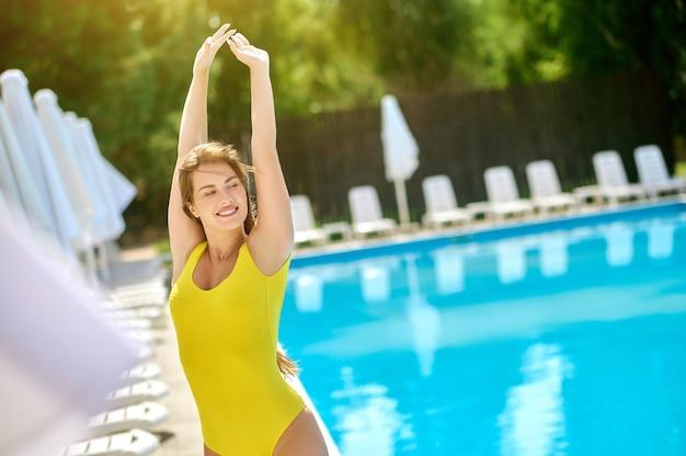 Een mooie jonge vrouw in een geel zwempak die zich voordeed bij het zwembad
