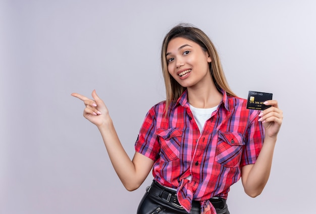 Een mooie jonge vrouw in een geruit overhemd die creditcard toont en met wijsvinger wijst