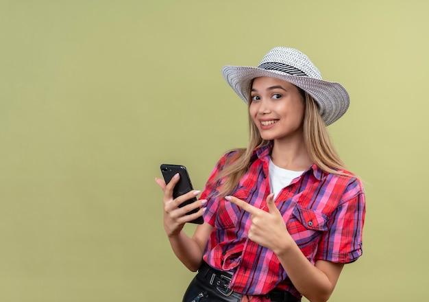 Een mooie jonge vrouw in een geruit overhemd die mobiele telefoon vasthoudt en er met wijsvinger naar wijst