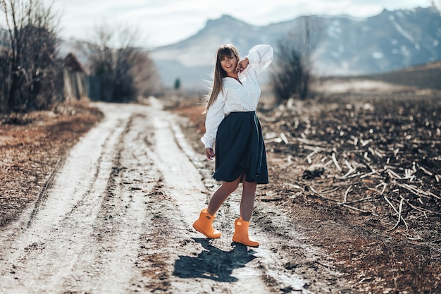 Een mooie jonge vrouw in een grijze rok en rubberlaarzen loopt door een weide in land. ze danst, lacht veel plezier en straalt vrijheid uit