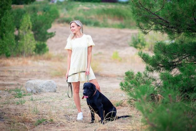 Een mooie jonge vrouw in een jurk loopt met haar labradorhond in een stadspark of in het bos.