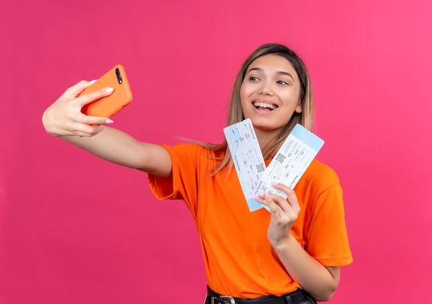 Een mooie jonge vrouw in een oranje t-shirt die glimlacht en selfie met mobiele telefoon neemt terwijl vliegtuigtickets op een roze muur worden getoond