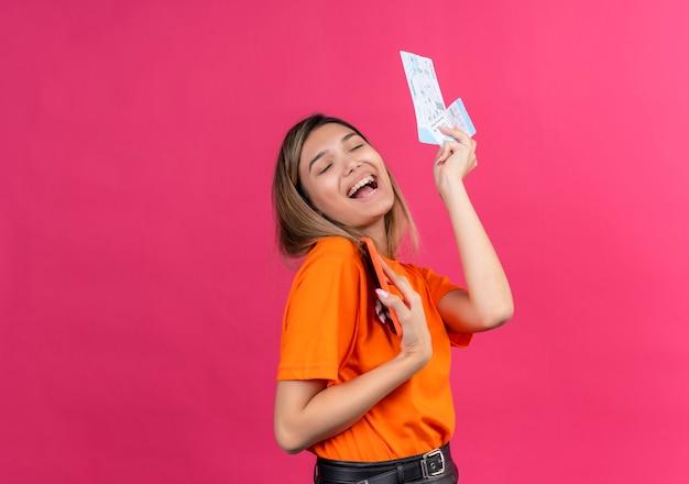 Een mooie jonge vrouw in een oranje t-shirt die glimlacht en zijn mobiele telefoon vasthoudt terwijl ze vliegtickets op een roze muur laat zien