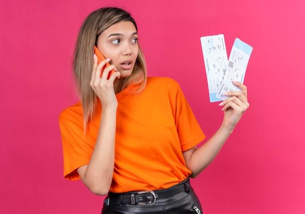 Een mooie jonge vrouw in een oranje t-shirt die op een mobiele telefoon praat terwijl ze vliegtickets op een roze muur vasthoudt