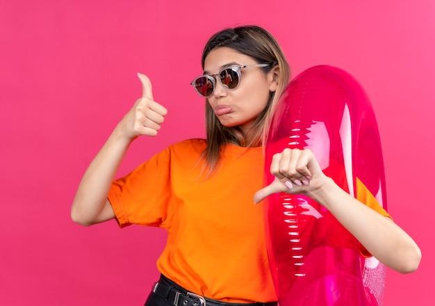 Een mooie jonge vrouw in een oranje t-shirt met een zonnebril die duimen op en neer laat zien terwijl ze een roze opblaasbare ring vasthoudt aan een roze muur